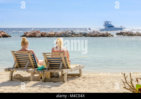 Two girls in a front row seats at the beach - Stock Photo