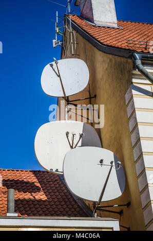 Satellite dish on the roof of an old building - Stock Photo