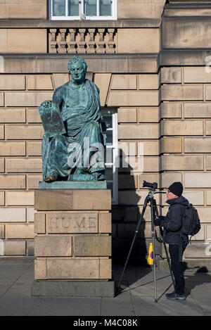 Statue of the philosopher and historian David Hume by sculptor Sandy Stoddart on Edinburgh's Royal Mile with a photographer. - Stock Photo