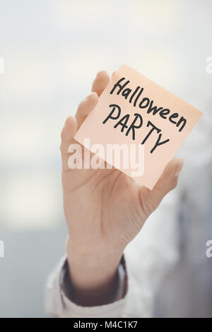 Woman holding adhesive note with Halloween party text - Stock Photo