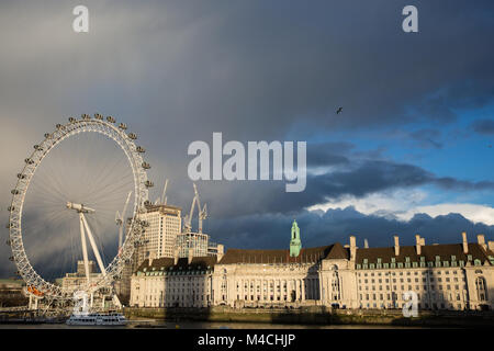 London, UK. 11th February, 2018. Striking late afternoon sunshine falls on County Hall and the London Eye against - Stock Photo