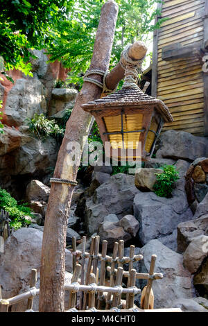 Rustic wooden lamp post tied with rope & old lamp hanging down. Picket fence in front & rocks, trees & part of shingled - Stock Photo