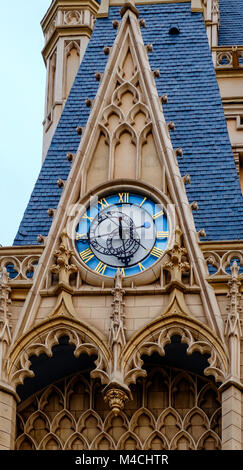 Blue clock with gold Roman Numerals as found on Cinderella's Castle at Disneyland Tokyo. Blue shingles in background. - Stock Photo