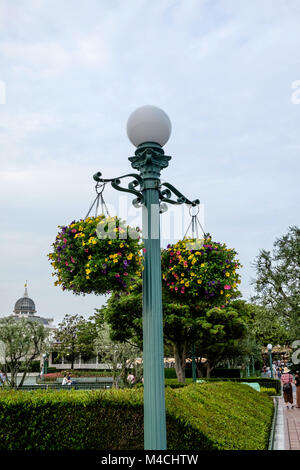 Ornate metal lamp post with round globe light on top with two baskets full of flowers hanging on either side. –Disneyland - Stock Photo