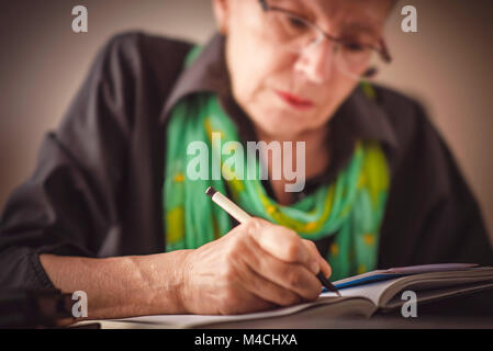 Writing an appointment in notebook - Stock Photo