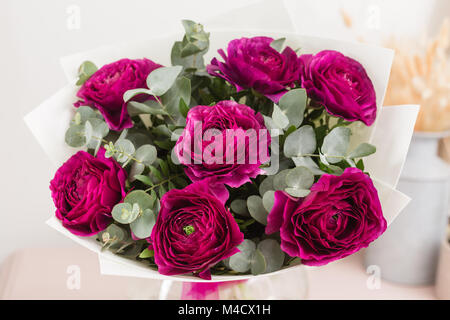 Persian buttercup. lace with many petals. Bunch violet ranunculus flowers light background. Wallpaper