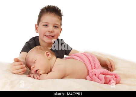 big brother and baby sister together happy and having fun in the nursery - Stock Photo