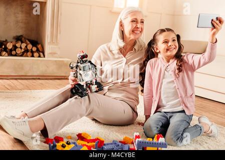 Smart little girl taking selfie with radiant grandmother - Stock Photo