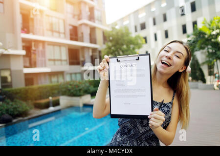 young girl proposes to sign contract to live in warm countries beautiful girl on background of pool suggests signing - Stock Photo