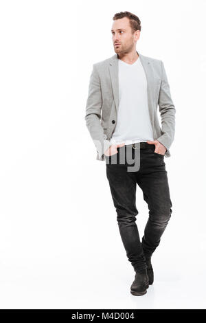 Full-length image of brunette businessman in jacket confidently posing on camera with hands in pockets and looking - Stock Photo