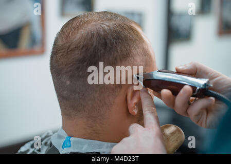 Man gets a cool haircut in barbershop. Barber cuts machine. - Stock Photo
