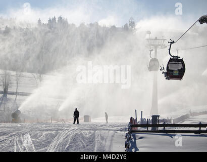 Willingen, Germany - February 7th, 2018 - Ski run with gondola lift and snow cannon shooting clouds of powdery snow - Stock Photo