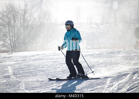 Willingen, Germany - February 7th, 2018 - Female skier in blue skiing suit on a ski run - Stock Photo