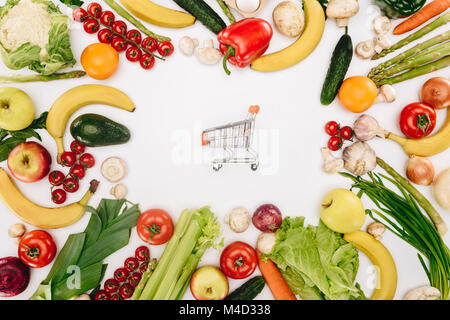 top view of shopping cart between vegetables and fruits isolated on white, grocery concept - Stock Photo