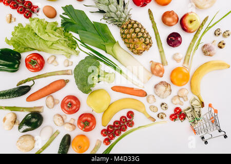 top view of small shopping cart with dollars and fruits with vegetables isolated on white - Stock Photo