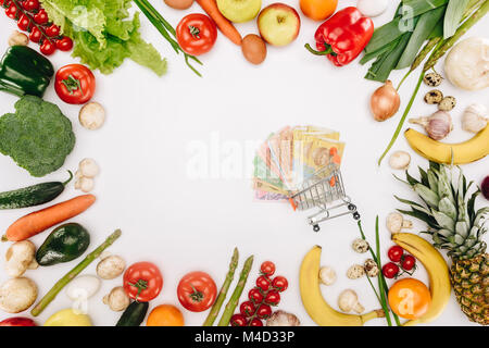 top view of shopping cart with cash between vegetables and fruits isolated on white - Stock Photo