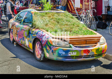 Car down Kensington Market covered in Grafitti and plants - Stock Photo