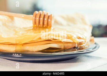Honey is poured on a stack of pancakes - Stock Photo