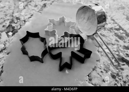 Three christmas cookie cutters beside flour in black and white. - Stock Photo