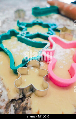 A little metal gingerbread man cookie cutter stuck in rolled out sugar cookie dough. - Stock Photo