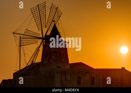 Windmill at sunset at the saltpans of Marsala in Sicily - Stock Photo