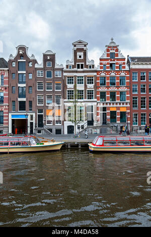 Colorful narrow row houses with retail space below on the canal in Amsterdam, Netherlands. Tourboats on the canal. - Stock Photo