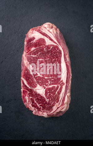 Raw dry aged Entrecote Steak on a slate - Stock Photo