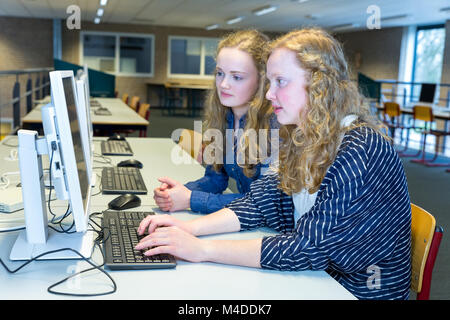 Two dutch students working on computer in school - Stock Photo
