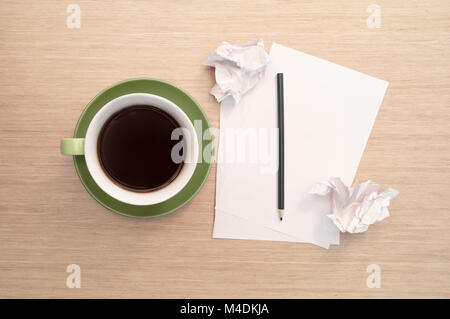 A green cup of coffee on the background of a table and a white blank piece of paper, a pencil and crumpled scraps - Stock Photo