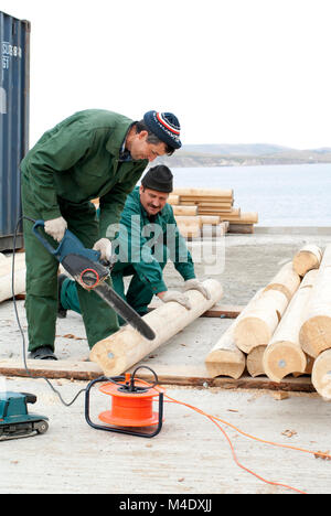 Carpenter saws a log on the construction of log cabin - Stock Photo