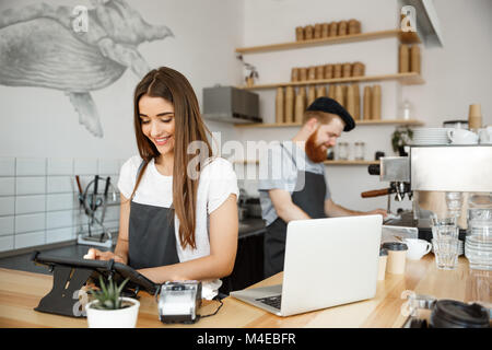 Coffee Business Concept - beautiful caucasian bartender barista or manager Posting order in digital tablet menu - Stock Photo
