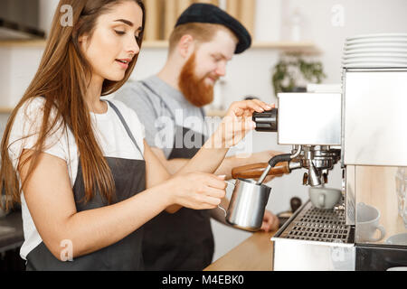 Coffee Business Concept - portrait of lady barista in apron preparing and steaming milk for coffee order with her - Stock Photo