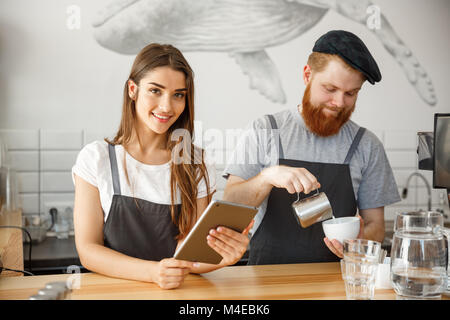 Coffee Business Concept - happy young couple business owners of small coffee shop working and planing on tablet. - Stock Photo