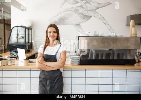 Coffee Business owner Concept - Portrait of happy attractive young beautiful caucasian barista in apron smiling - Stock Photo