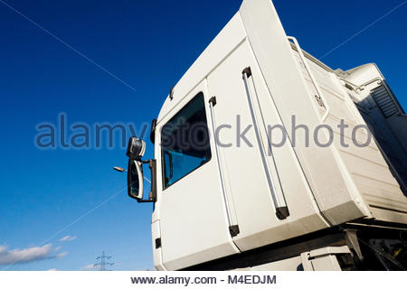 White cargo truck delivering goods cabin against blue sky - Stock Photo