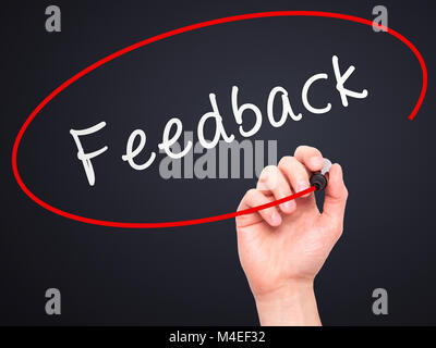 Man Hand writing Feedback with marker on transparent wipe board - Stock Photo