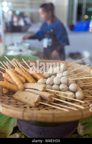Thai snack: meat balls, fish balls and sausages are steaming on wooden tray. - Stock Photo