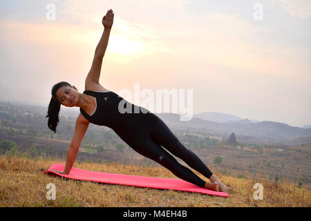 Young Indian girl doing fitness exercise with mountain backdrop Side Plank Pose Near Mountain, Pune, Maharashtra. - Stock Photo