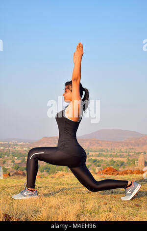young indian girl doing yoga  vrikshasana with mountain