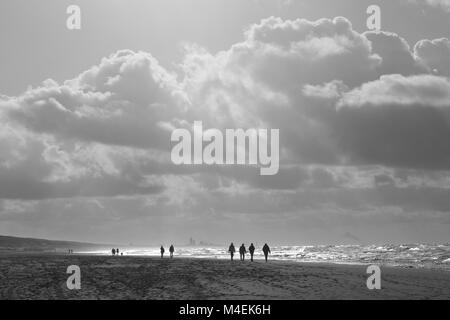 Backlight  capture of silhouetted walkers on the beach at Katwijk, South Holland, The Netherlands, Europe. - Stock Photo