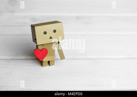 Little robot character Danbo standing on wooden floor with red heart in hand - Stock Photo