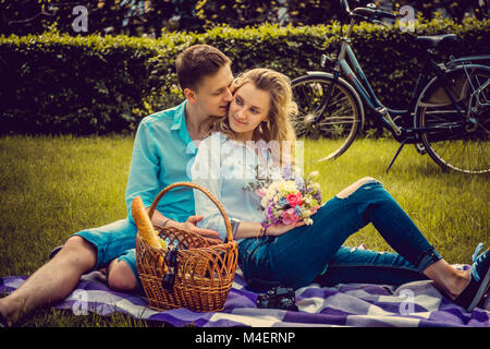 Lovely couple on picnik in a park in summer sunny day. - Stock Photo