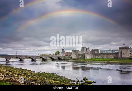 Rainbow over King Johns Castle - Stock Photo