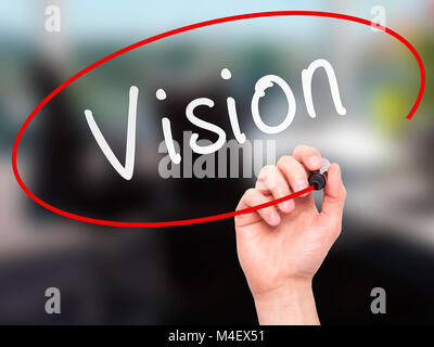 Man Hand writing Vision with marker on transparent wipe board - Stock Photo