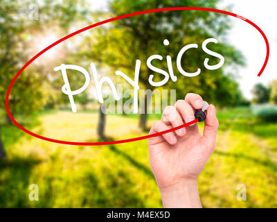 Man Hand writing Physics with black marker on visual screen - Stock Photo