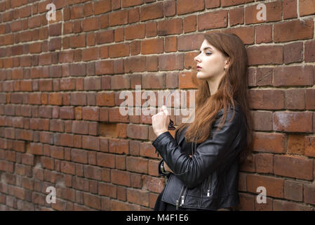Girl with long hair near an old brick wall - Stock Photo