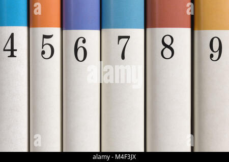 Six colored numbered books in a row - Stock Photo