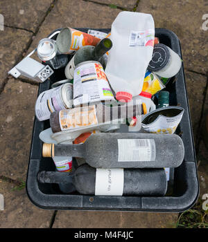 Frost-covered recycling box of glass, plastic and metal awaiting collection outside a Shropshire house. - Stock Photo