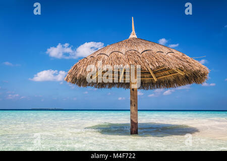 Tropical sandbank island with sunshade umbrella. Indian Ocean, Maldives. - Stock Photo