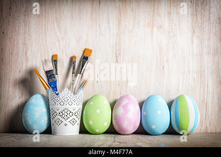 Pastel Easter eggs and brushes in a rustic cup - Stock Photo